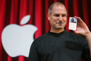 "Apple Computer Inc. CEO Steve Jobs holds up the new iPod showing an episode of hit television show ""Desperate Housewives"" showing, during an unveiling in San Jose, Calif., Wednesday, Oct. 12, 2005. (AP Photo/Paul Sakuma)"